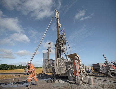Workers operating drilling rig to explore for coal in field - p429m860141f by Monty Rakusen