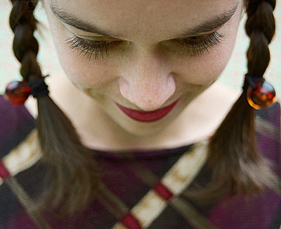 Young woman with pigtails looking down - p6750032 by Mieke Dalle