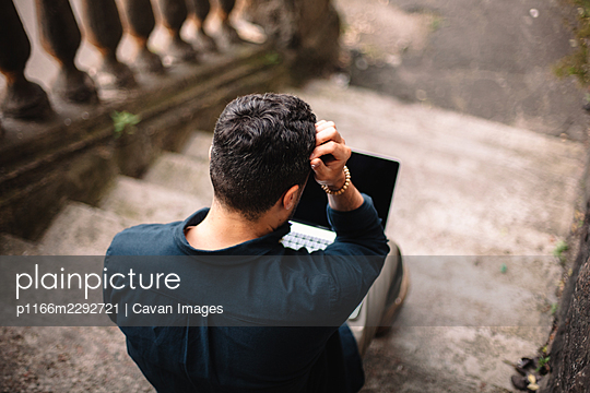 Businessman using laptop computer sitting on steps in city - p1166m2292721 by Cavan Images