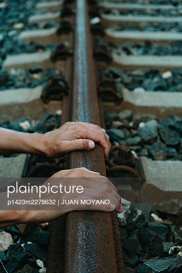 Man grips the rusty rail of a railway track - p1423m2278632 by JUAN MOYANO