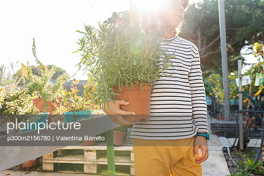 Boy with potted plant at plant nursery - p300m2156780 by Valentina Barreto