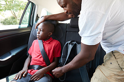 Father fastening seat belt for son in back seat of car - p1023m2238496 by Himalayan Pics