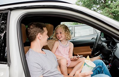 girl laughing with her dad sat in the car playing on a cell phone - p1166m2137037 by Cavan Images