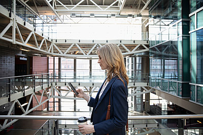 Businesswoman with coffee using smart phone on office atrium balcony - p1192m2093808 by Hero Images
