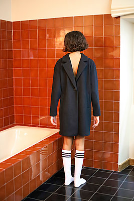 Young woman with jacket upside down and socks in bathroom - p1521m2128950 by Charlotte Zobel