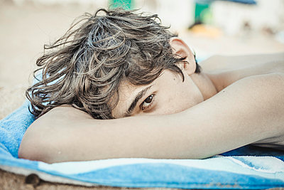 Teenager lying on a beach  - p445m2045673 by Marie Docher