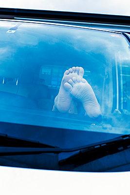Person mit nackten Füßen hinter einer Windschutzscheibe - p1271m2055350 von Maurice Kohl