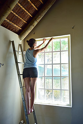 Young woman renovating her home working at window frame - p300m2079219 by Eyecatcher.pro