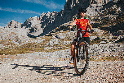 Woman with mountain bike at Picos de Europa National Park on sunny day, Cantabria, Spain - p300m2240207 by David Molina Grande