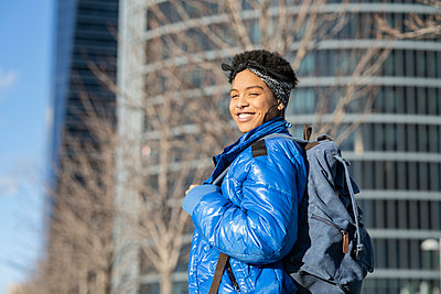 Happy young woman with backpack in city on sunny day - p300m2265866 by Jose Carlos Ichiro