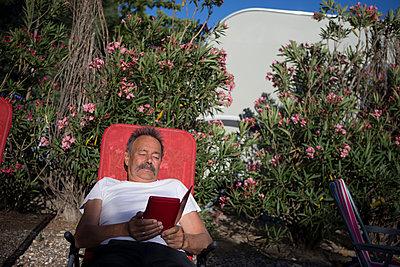 Mann liest Buch im Liegestuhl - p505m1195404 von Iris Wolf