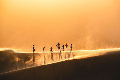 Walvis Bay, Namibia, Africa. People walking on the edge of a sand dune at sunset. - p651m2033386 by Marco Bottigelli