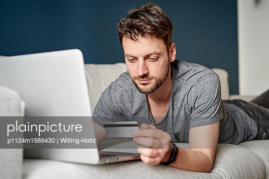 Junger Mann macht Online-Shopping auf dem Sofa - p1124m1589430 von Willing-Holtz