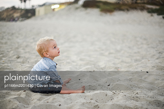 Little boy playing with sand on a California beach - p1166m2201430 by Cavan Images