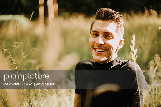 Young man sitting in the meadow - p1267m2259741 by Jörg Meier