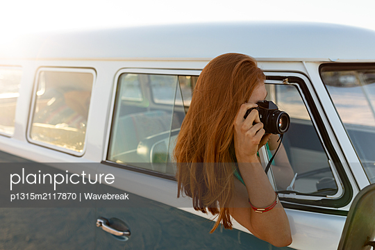 Woman taking picture with digital camera out of window of a camper van - p1315m2117870 by Wavebreak