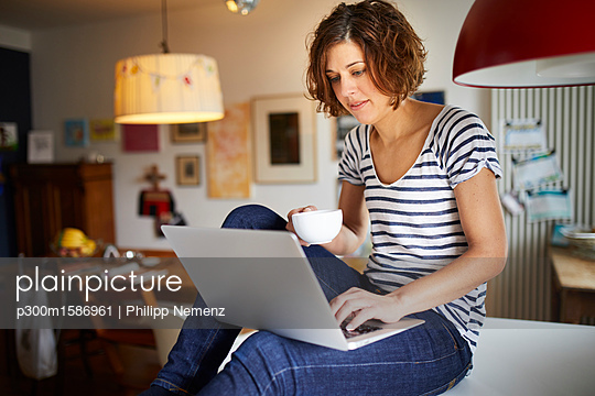 Portrait of mature woman sitting on kitchen table using laptop - p300m1586961 von Philipp Nemenz