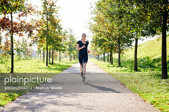 Young woman running in a park - p300m2004312 von Markus Mielek