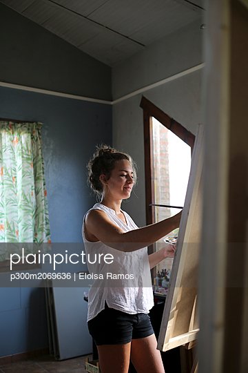 Smiling young woman painting in her atelier - p300m2069636 by Eloisa Ramos