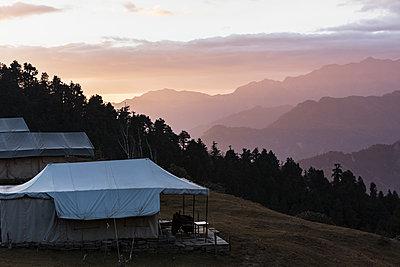 Yurts overlooking silhouetted mountains, Jaikuni, Indian Himalayan Foothills - p1023m2024449 by Martin Barraud