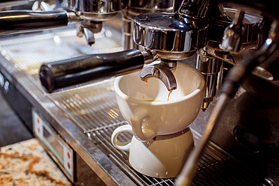 Espresso machine pouring coffee into cup at cafe - p1166m1144822 by Cavan Images