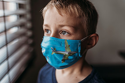 Portrait of young school aged boy with mask on with at home - p1166m2207800 by Cavan Images