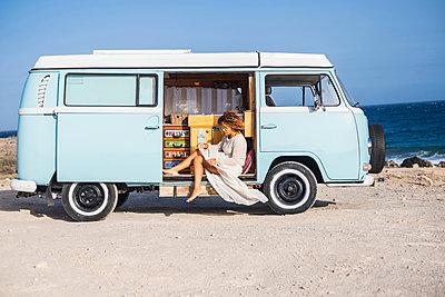 Spain, Tenerife, woman sitting in van parked at seaside - p300m1505897 by Simona Pilolla