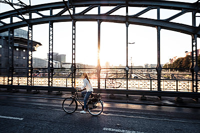 Young cyclist on a bridge at sunset - p300m2144876 by Wilfried Feder