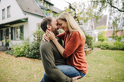 Happy couple kissing in garden, in front of their dream house - p300m2166680 by Kniel Synnatzschke