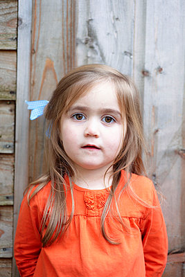 Young girl standing outside wooden shed - p3493821 by Wayne Kirk