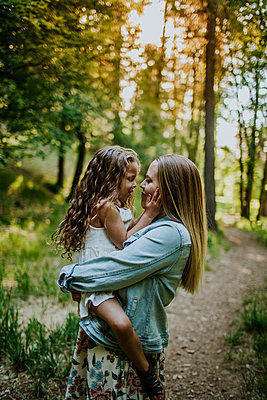 Happy mother holding young girl in forest - p1166m2201887 by Cavan Images