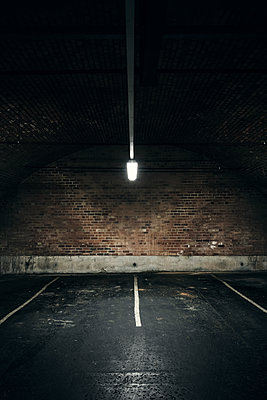 Empty underground car park illuminated by a single overhead light - p1280m2089692 by Dave Wall