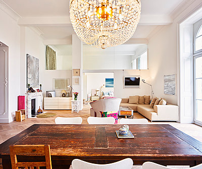 Living room in a refurbished old building with dining table in the foreground - p300m1029051f by Dieter Schewig