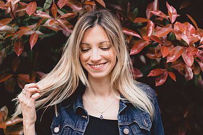 Portrait of happy young woman in autumn - p300m1581127 von VITTA GALLERY