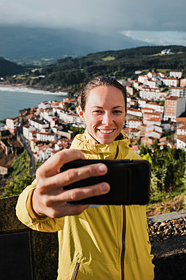 Smiling woman taking selfie with village through smart phone during vacations - p300m2225169 by David Molina Grande