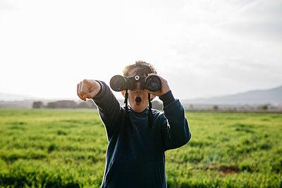 Spain, Barcelona. Boy in the field using binoculars. - p300m2275608 von Josep Rovirosa