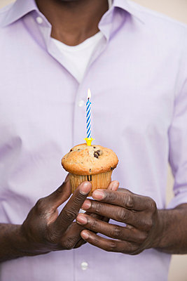 Man holding muffin with single candle on top - p301m844124f by Paul Hudson