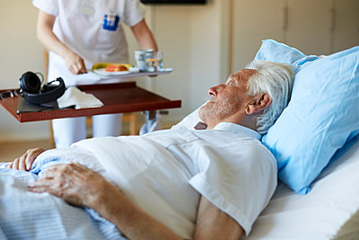 Senior man looking at female nurse serving breakfast while lying on hospital bed - p426m1494045 by Maskot