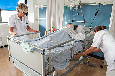 Nurses adjusting patients hospital bed - p429m1198241 by Arno Masse