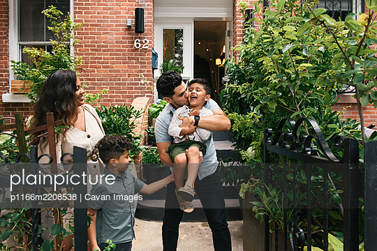 Family playing and laughing together in front of brownstone home - p1166m2208538 by Cavan Images