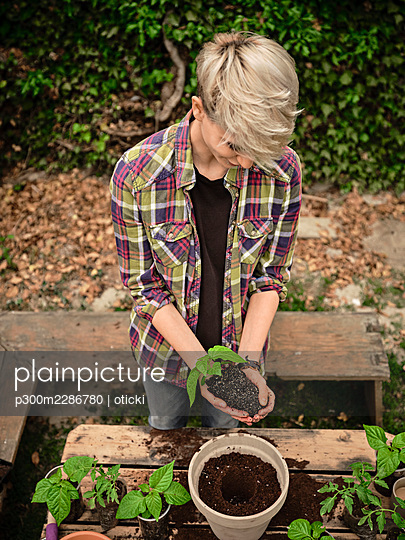 Serbia, Vojvodina. Young woman holding small pepper plant in hands while planting - p300m2286780 von oticki