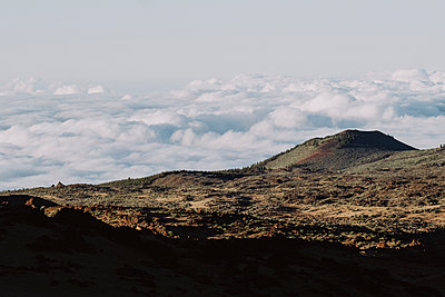 Pulled back view of volcanic landscape over the clouds - p1166m2124308 by Cavan Images