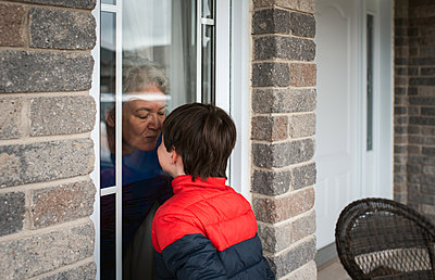 Young boy looking through window at grandma during Covid 19 pandemic. - p1166m2174170 by Cavan Images