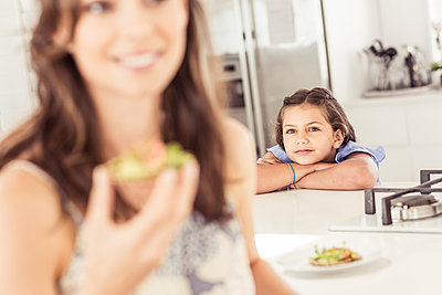 Portrait of a girl leaning on kitchen counter with mother in foreground - p300m2167517 by Floco Images