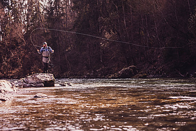 Mid adult man standing on rock catching fish from river - p300m2220686 by Studio 27
