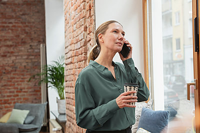 Middle aged woman, business owner, talking on cell phone next to the window of her office. Munich, Germany - p300m2273802 von Studio 27