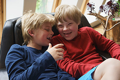 High angle view of happy brothers sitting on chair at home - p301m1180555 by Halfdark
