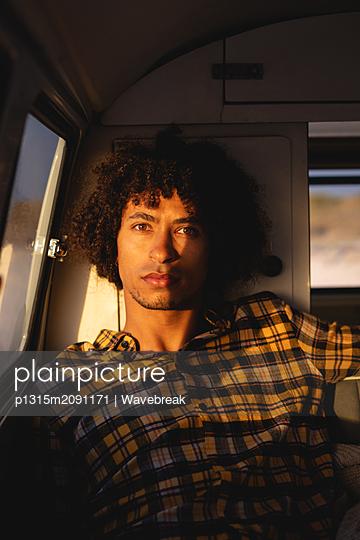 Man sitting in camper van and looking at the camera  - p1315m2091171 by Wavebreak