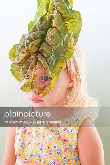 Child loooking through a leave - p1514m2133278 by geraldinehaas