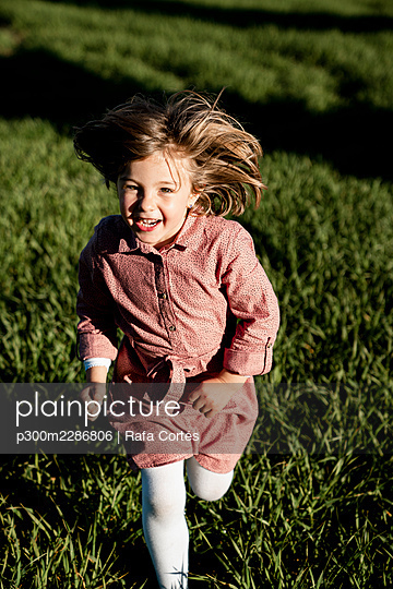 Cheerful little girl running on agricultural field during sunny day - p300m2286806 by Rafa Cortés